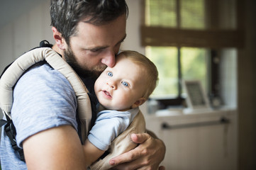 Man kissing son in baby carrier