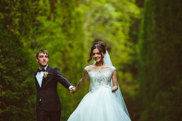 handsome and young groom and his beautiful bride walking in the