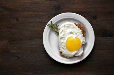 Aluminium Prints Egg fried egg with rosemary on a white plate