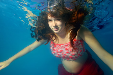 Pregnant girl swims underwater with her hair on blue background looking to the camera. Portrait. Close-up. The view from under the water. Horizontal orientation