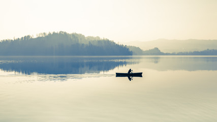 Zen on the lake. Fog over the lake. In calm water reflection mirror. Man with a paddle in the boat.