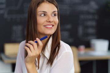 lächelnde junge frau sitzt am schreibtisch und schaut zur seite