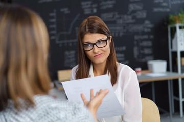 frau in einer besprechung schaut ihre chefin unglücklich an