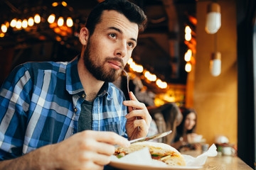 Handsome young man having lunch in elegant restaurant alone