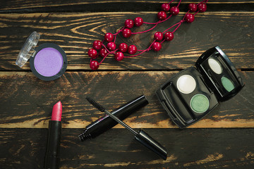Color cosmetics makeup and red beads on a wooden table