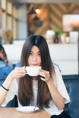 Happy asian female with latte coffee in cafe during free time