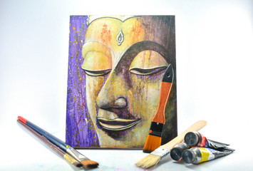 The brushes painting, color tubes and orange Buddha's head picture