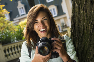 Beautiful woman at the park with a camera. Smiling and taking photos.