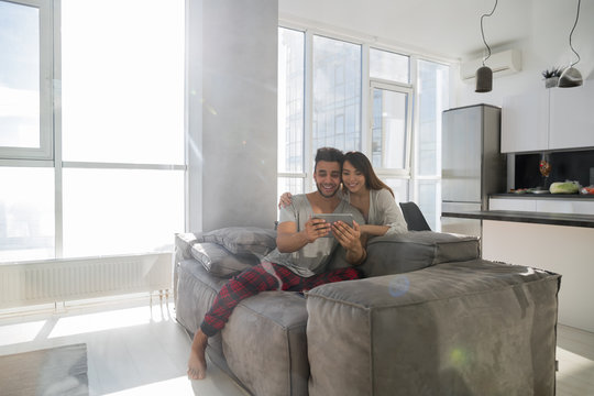 Happy Couple Sitting On Couch Using Tablet Computer Modern Apartment With Panoramic Window, Mix Race Man Woman Embracing
