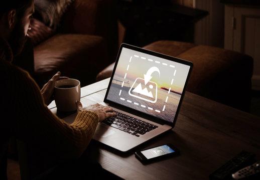User with Laptop in Dark Room Mockup