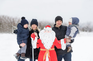 Young Family and Santa Claus In Snow Scene