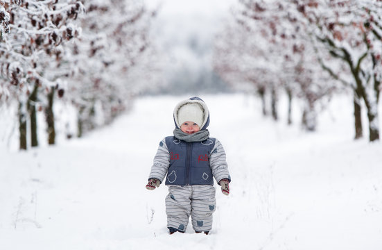 Little kid in snowsuit, hat and scarf, walking through a snowy path