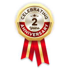 Red celebrating 2 years badge, rosette with gold border and ribbon
