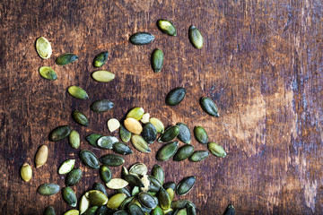 ..Pumpkin seeds over wooden table with copy space.