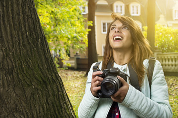 Beautiful woman at the park with her camera taking photos. Surprised look on her face.
