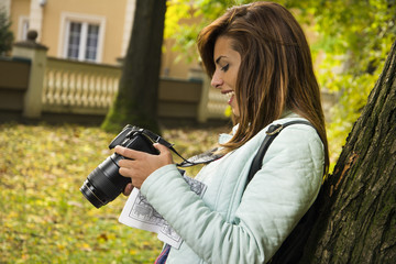 Young girl holding a camera and laughing at the park.