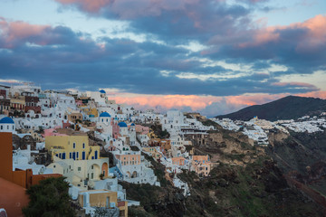 White city on a slope of a hill at sunset, Oia, Santorini, Greec