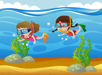 Two kids diving under the ocean