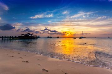 Fototapete - Sun goes down over Palm Beach, Aruba