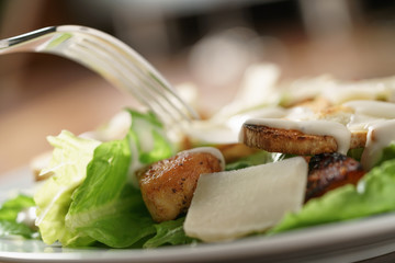 closeup shot of caesar salad with chicken on old wooden table