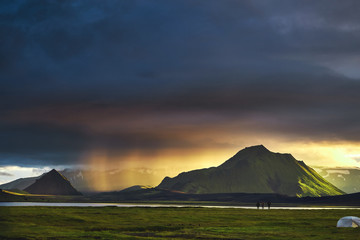 Travel to Iceland. Beautiful Icelandic landscape with mountains, sky and clouds. Trekking in national park Landmannalaugar. Rainy and cloudy Evening in Camping near Alftavatn lake. Tents and hikers in