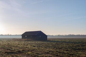 Old barn in misty farmland. Achterhoek. Gelderland. The Netherla