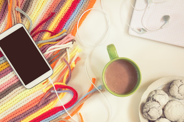 Office desk with cup of hot chocolate, phone, notebook, checkered scarf and chocolate cookies. Flat lay white background. Coloring and processing photo.