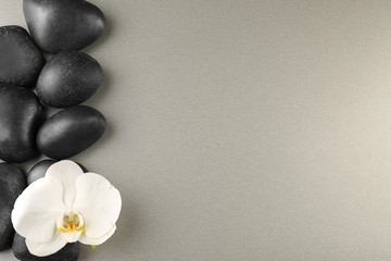 Fotobehang Spa stones and orchid flower on color background
