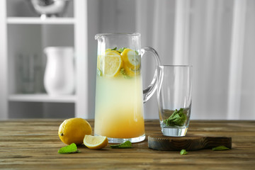 Glass jug with lemonade on wooden table