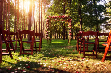 wedding arch decorated with flowers in green forest. picture wit
