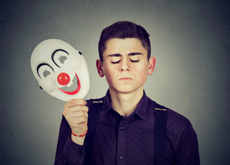 Sad man taking off happy clown mask. Split personality