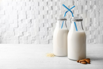 Bottles of sesame and almond milk with straws on wooden table against white blurred background