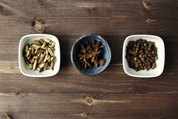 Cardamom, anise, allspice in ceramics bowls on wooden table. Cui