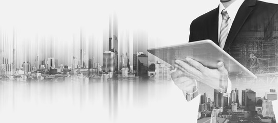 Businessman working on digital tablet, with double exposure city and real estate site construction, business development concept