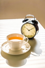 Clock and tea on office desk