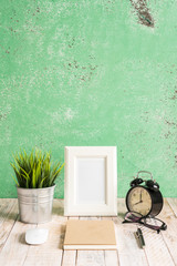 Wooden workplace desktop with clock; plants; glasses; Frame and