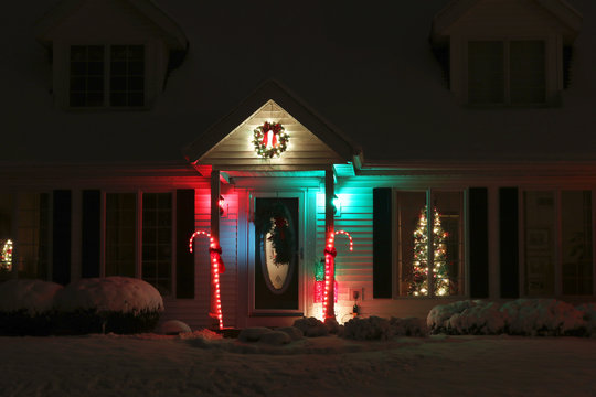 Seasonal house outdoors decoration. House main entrance and front yard, covered by fresh snow decorated for Christmas and New Year Holidays. Decorated christmas tree in the window. Night scene.