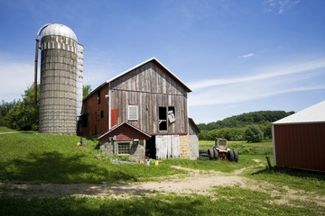 Agricultural background. A farm at Midwest USA. Wisconsin rural landscape with old farm buildings and utensils.