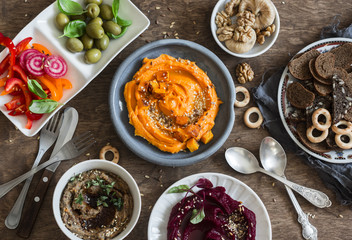 Vegetarian snack. Pumpkin, beets hummus, beans and mushroom pate, vegetables, nuts, bread on a wooden table, top view. Flat lay. Vegetarian, healthy food concept