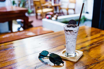 Milkshake with cookies and cream frappe on wood table in cafe