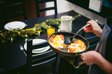 Woman puts homemade food. Female hands carefully applied to fried egg dish from  pan. breakfast for two persons, at home in kitchen at dining table