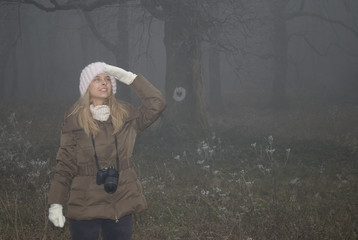 Pretty young woman looking far away in fog forest looking at the trail of a fairytale magic in a foggy winter day holding dslr camera
