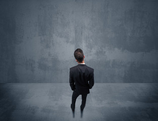 Businessman standing in front of urban wall