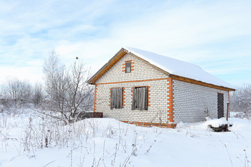 Abandoned unfinished brick house in a snow-covered field