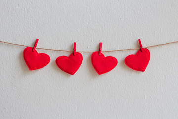 Red heart decoration hanging over wall background, Valentine day concept.