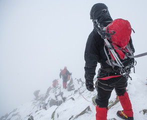 Alpinists in mountains. Team work.