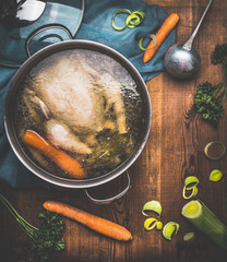 Chicken soup cooking, pot with chicken broth and  ladle on dark rustic wooden background with vegetables ingredients, top view. Healthy food or Diet nutrition concept