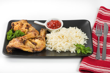 Grilled chicken thighs with rice on the table with cutlery