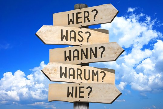 """Signpost - questions - """"Wer?"""", """"Was?"""", """"Wann?"""", """"Warum?"""", """"Wie?"""" (German)/ """"Who?"""", """"What?"""", """"When?"""", """"Why?"""", """"How?"""" (English)."""