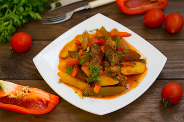Stew with potatoes, carrots, pickles, tomatoes and hot peppers. Azu by Tartarian on a white square plate. Wooden rustic background. Top view. Close-up